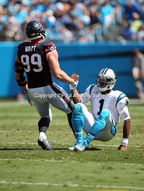 Carolina Panthers quarterback Cam Newton (1) gets a lending hand from Houston Texans defensive end J.J. Watt (99) while getting up off the grass during the 2015 NFL week 2 regular season football game against the Houston Texans on Sunday, Sept. 20, 2015 in Charlotte, N.C. The Panthers won the game 24-17. (©Paul Anthony Spinelli)