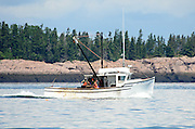 Two fishermen in orange raingear on a white fishing boat sailing past pink granite ledges and spruce forest.