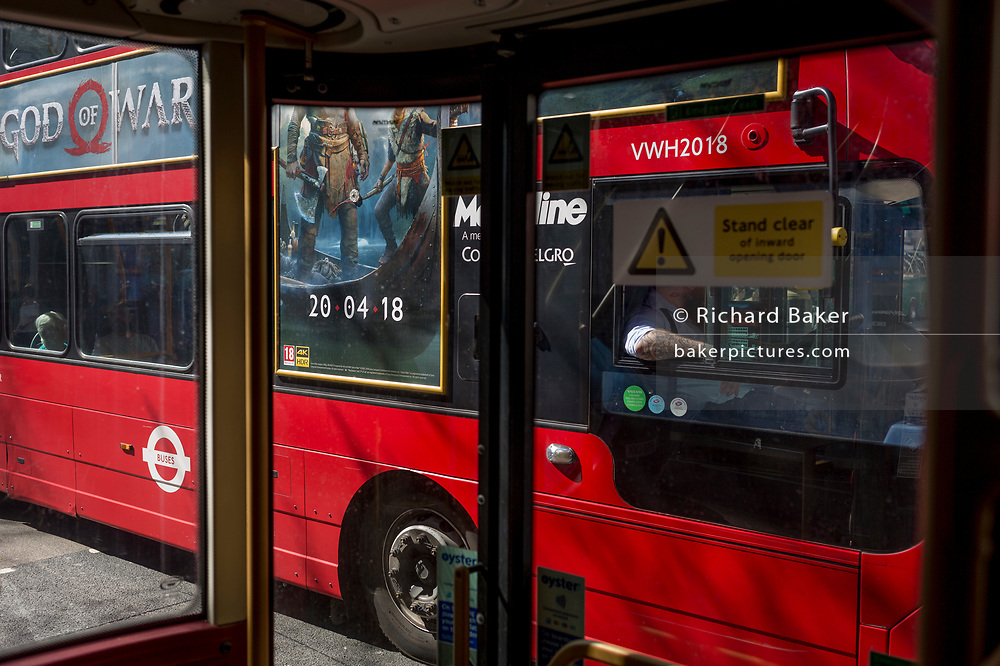 The tattooed arm of a bus driver and an ad for a new Playstation game called God of War, on 19th April 2018, in London, England.