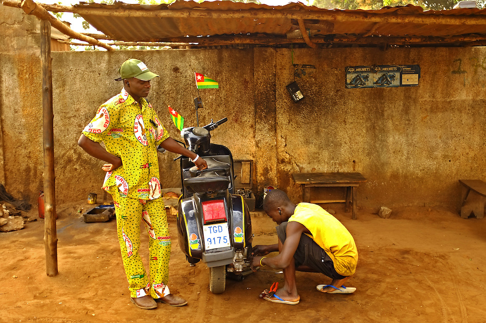 LOME, TOGO  13-02-03   -  Josue Tomdje, dressed in traditional fabric with a Sparrow Hawk motif, waits for his motorcycle to be repaired by a mechanic before the African Cup of Nations (ACN) quarter-final match between Togo and Burkina Faso on February 3, 2013. Photo by Daniel Hayduk