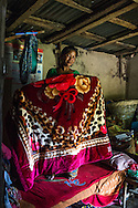 Kalpana Tamang (40), holds up the winter blanket that was provided to her in the earthquake relief 'Home-in-a-Box' tin trunk by SOS Childrens Villages in her temporary shelter in Kavre, Bagmati, Nepal on 30 June 2015.  Kalpana, a widow with 3 children, has been supported by SOS Children's Villages for many years now and had receive the Home-in-a-Box after the earthquake destroyed her house, almost killing her two daughters. She now lives in a temporary shelter, sharing her dwelling with farm animals, and is trying to make ends meet by weaving bamboo baskets to supplement the financial assistance provided by SOS Childrens Villages. The NGO mostly supports her children's welfare and schooling as well as provides her with essential household and schooling items like kitchen utensils and school books and uniforms. Photo by Suzanne Lee for SOS Children's Villages