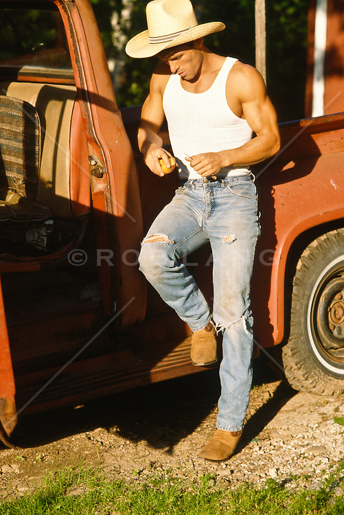 Muscular good looking cowboy peeling an apple leaning against a truck