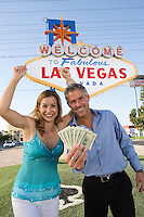 Mid-adult couple in front of Welcome to Las Vegas sign, portrait
