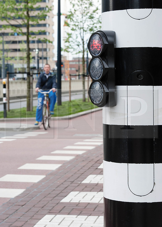 © Licensed to London News Pictures. 07/04/2014. Rotterdam, The Netherlands. Dutch cyclists cycling on the 'fietspad' (bike paths physically separated from the main roadway) alongside special cyclist-specific traffic lights.  On Thursday April 3rd a london cyclist was killed by a waste lorry turning at a junction in Central London, the third cyclist to die in the capital so far this year.    Dutch cyclists benefit from safer road conditions than their London counterparts as a result factors such as these cycle lanes. Photo credit : Richard Isaac/LNP