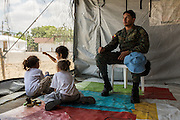 2016/07/27 – Portoviejo, Ecuador: Corporal Quiroz of the Ecuadorian army, looks after some children while their mothers went to collect food on the communal kitchen of the shelter in Portoviejo, Ecuador, 27th July 2016. The shelters are managed and operated by the army and they try to help the families that live there and that have lost everything on the 16th April earthquake. (Eduardo Leal)