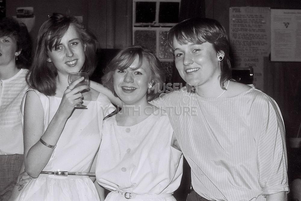 Girls posing at a party, London, UK, 1984