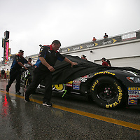 Crew members push the JPO Absorbents Ford of driver Michael McDowell through the wet garage area prior to the 56th Annual NASCAR Coke Zero400 race at Daytona International Speedway on Saturday, July 5, 2014 in Daytona Beach, Florida.  (AP Photo/Alex Menendez)