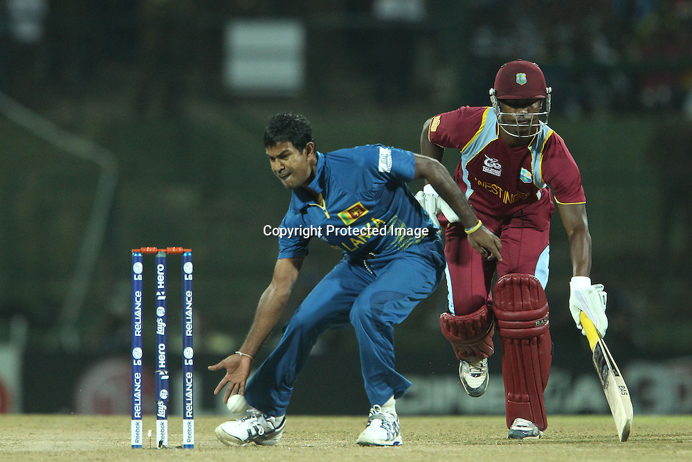 Nuwan Kulasekara gathers the ball as Johnson Charles of The West Indies makes his ground during the ICC World Twenty20 Super 8s match between Sri Lanka and The West Indies held at the  Pallekele Stadium in Kandy, Sri Lanka on the 29th September 2012<br /> <br /> Photo by Ron Gaunt/SPORTZPICS