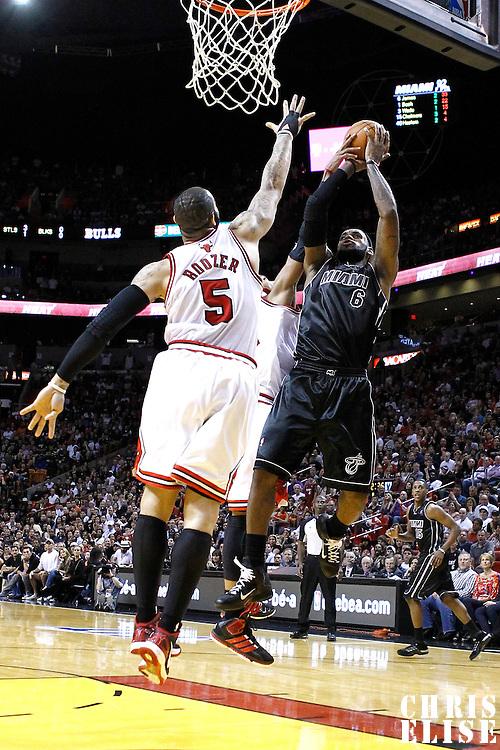 29 January 2012: Miami Heat small forward LeBron James (6) takes a jumpshot over Chicago Bulls power forward Carlos Boozer (5) during the Miami Heat 97-93 victory over the Chicago Bulls at the AmericanAirlines Arena, Miami, Florida, USA.