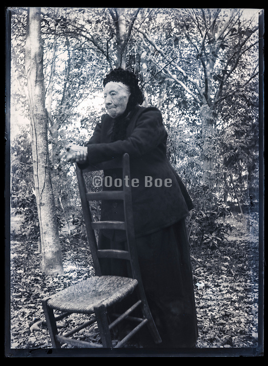 senior woman in garden setting France ca 1920s