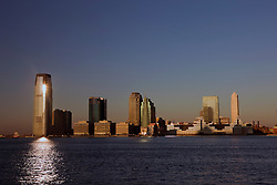 Exchange Place North / Jersey City, New Jersey skyline at sunrise viewed across the Hudson River from Manhattan, New York City, New York.