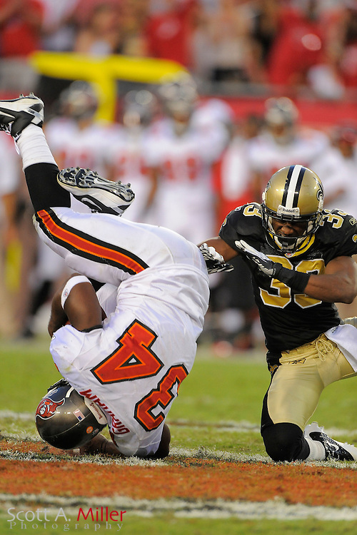 Tampa Bay Buccaneers running back Earnest Graham (34) is tackled by New Orleans Saints cornerback Jabari Greer (33) after flipping in mid air during the Bucs 26-20 win at Raymond James Stadium on Oct. 16, 2011 in Tampa, Fla...©2011 Scott A. Miller