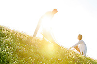 Tilt image of young couple spreading picnic blanket on grass during sunny day