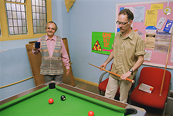Two men with learning disabilities standing around pool table in community centre,