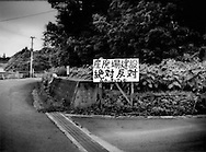 Hand-painted sign protesting a proposal to dump radiation contaminated tsunami debris up this road right on the 20 km (12.4 miles) nuclear no-entry zone line.  Near Kobama, Fukushima Prefecture, Japan.