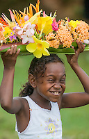 A shy Solomon Islands girl, caught carrying a flower arrangment on her head, breaks into a giggling fit. Travel photographer: Djuna Ivereigh.