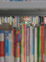 Boy reading book behind bookshelf in library