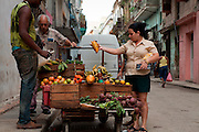 A woman purchases fruit from a street vender in Old Havana. Such small private business ventures have only recently been permitted by Cuba's communist government.