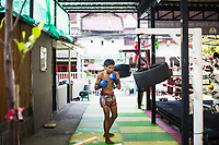 A young Thai fighter punches hanging tires at Sor Dechapant Gym in Bangkok, Thailand. In recent years, combat sports--especially Muay Thai--have been seen as a crucial elements in successful Mixed Martial Arts fighting.