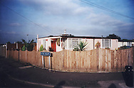"""The Catford prefabs estate in South London, 2004. Thousands of post-war prefabs are still being lived in and cherished by their tenants or owners all over the UK. I  love prefabs. Some people will think living in a prefab is like living in a box. Yes, it might sound or even look a bit like that but what a lovely, sophisticated box! I am talking about post-war prefabs, erected in a hurry just after the war when Britain was suffering an unprecedented housing shortage. More than 150 000 of these prefabricated houses were erected all over the UK mainly ins small estates. They were luxury to most of the residents who mainly were service men coming back from the war and reuniting with their family. Their prefab became their little castle with all mod cons and even more than any working class could hope for at the time: hot water, toilets inside, a fitted kitchen with a gas fridge and a garden all around the house. Part of the temporary housing programme, they were not supposed to last over a decade. Yet, over 70 years later, a few Thousands are still standing and very much loved.<br /> <br /> Why do people love their prefab so much, why are they so attached to their """"cardboard or tin boxes""""? Is it the layout of the prefab, the design of the interior, the garden around? Is the sense of community they created? Or a combination of everything?That's what I have been trying to find out for the last 11 years, since I started taking pictures of prefabs in South London. I have travelled all over the UK, from Redditch to Newport, Chesterfield, Catford and even on the Isle of Lewis to try to draw some answers. I have met wonderful people and come back with their portraits and their moving stories. Here they are for you to discover through this project."""