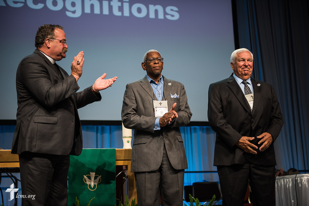 The Rev. Dr. Matthew C. Harrison, president of the LCMS, helps recognize outgoing Board of Directors members, the Rev. Victor Belton and Warren Puck, on Tuesday, July 12, 2016, at the 66th Regular Convention of The Lutheran Church–Missouri Synod, in Milwaukee. LCMS/Frank Kohn