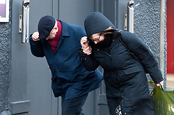© Licensed to London News Pictures. 8/02/2016. Porthcawl, Bridgend, Wales, UK. A man and woman battle against the wind in Dock Street. People struggle to stay on their feet in winds gusting over approximately 60mph. Storm Imogen batters the small Welsh seaside resort of Porthcawl in the county borough of Bridgend on the South coast of Wales, UK. Photo credit: Graham M. Lawrence/LNP