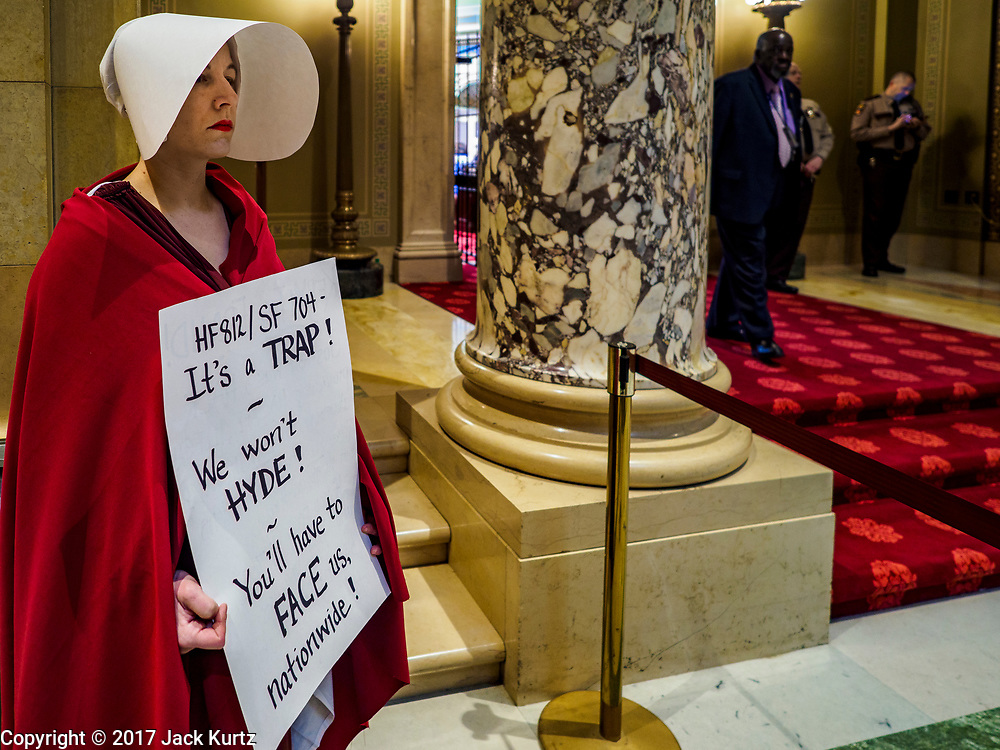 "04 MAY 2017 - ST. PAUL, MN: A woman dressed as a handmaid (from the novel and Hulu series ""A Handmaid's Tale"") stands at the entrance to the Minnesota State Senate chamber. About 50 people came to a protest to urge Minnesota State Senators to vote against two bills supported by the Republican party that would restrict access to women's health care in Minnesota. The protest was organized by  NARAL Pro-Choice Minnesota, NCJW Minnesota, and Planned Parenthood Minnesota. The Senate passed the bills but Minnesota's Democratic governor is expected to veto the legislation when it reaches his desk.     PHOTO BY JACK KURTZ"