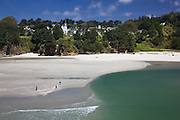 hillside church and people walking dogs on the beach in mendocino california,