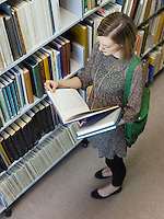 Young woman looking through book in library view from above