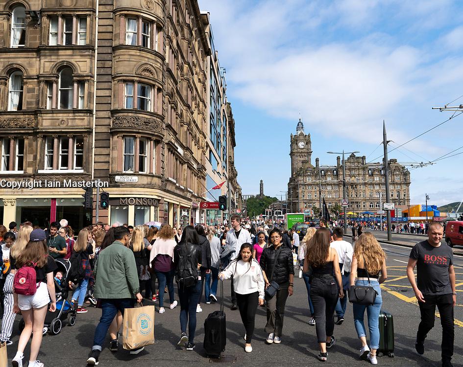 Pedestrians crossing street at Princes Street in Edinburgh, Scotland, UK
