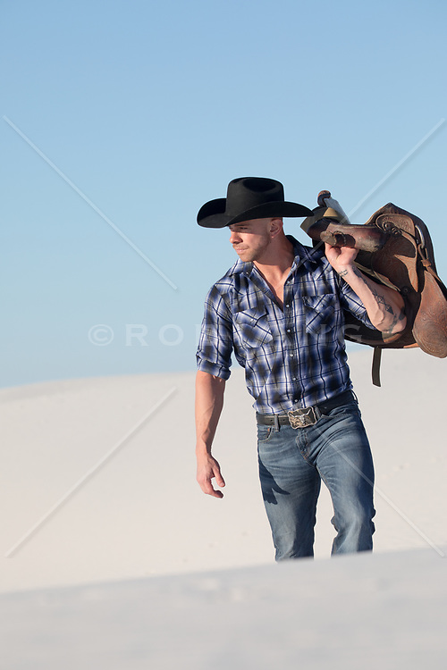 muscular cowboy holding a saddle