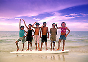 Local children swimming with surfboard on Isla de Holbox, Mexico.