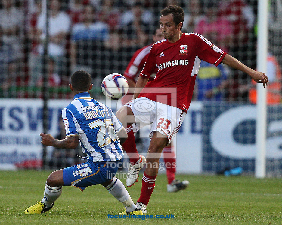 Picture by Paul Terry/Focus Images Ltd +44 7545 642257.14/08/2012.Raffaele De Vita ( R ) of Swindon Town and Liam Liam Bridcutt of Brighton and Hove Albion during the Capital One Cup match at the County Ground, Swindon.