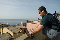 Man ties shoes to start the Cinque Terre hike from Vernazza to Monterosso.
