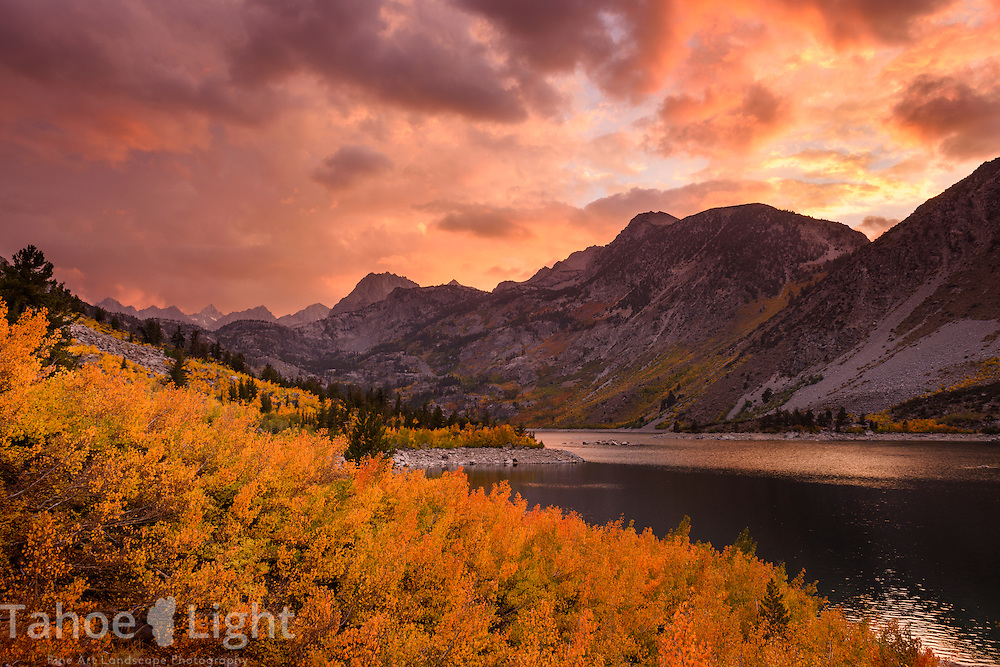 Fall color in the High Sierra up the Bishop Creek drainage at Lake Sabrina. The fields of aspen are turning gold and red and a first day of fall storm moved through creating a beautiful moody sunrise.
