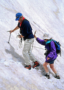 "A mountain guide from Robinson Expeditions escorts a client with rope and ice axe across a steep snow gully on a traverse of Mount Smolikas, second highest mountain in Greece. Hike the North Pindus Mountains (Pindos or Pindhos) around Zagoria, Epirus/Epiros, Greece, Europe. Zagori (Greek: ) is a region and a municipality in the Pindus mountains in Epirus, in northwestern Greece. Zagori contains 45 villages collectively known as Zagoria (Zagorochoria or Zagorohoria). Published in ""Pindos: The National Park"" (2010) by Alexander G. Tziolas, preface by Tom Dempsey et al, ISBN 978-960-98795-3-8."