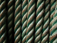 a coil of hawser rope on a Washington State Ferry showing repeating lines of thick strands making up the rope coils. The rope is new but showing the first signs of wear and a layer of rust from the deck colors the abraded parts.