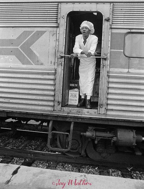 The Amtrak Floridian passenger train that operated between Chicago, Illinois and Miami, Florida ceased operation in 1979.  It was the last passenger train that serviced Louisville. Kentucky as well.  These photographs document the final days for the workers in the Chicago Yards, the Amtrak employees aboard the train, an engineer,, W.C. Roddy, that drove the train between Louisville and Bowling Green, KY and the passengers who enjoyed riding the rails.<br /> <br /> Pictured: In Jacksonville, Florida, the train splits, with part going to St. Petersburg and the other section continuing on to Miami.  During the stop a cook watches from the kitchen car for a co-worker to return with supplies for the remainder of the Miami-bound trip.