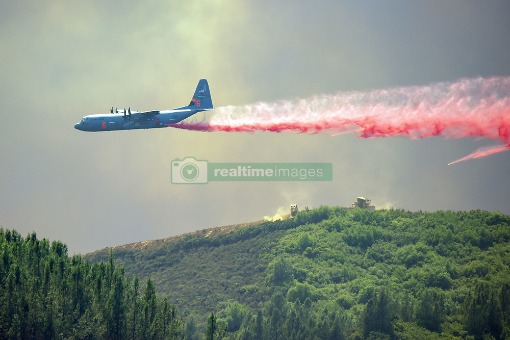 August 1, 2018 - Lakeport, California, US - A C-130 Air Tanker drops fire retardant on a ridge West of Scotts Valley Road near Lakeport, California to help hold a dozer line attempting to slow the spread of the River Fire burning in Lake and Mendocino Counties. The River Fire is one of two fires making up the Mendocino Complex Fire burning in northern part around the west end of Clear Lake, but both fires, the Ranch to the north and the River to the south, are still large and growing. Together they now total 90,912 acres and are still only 24% contained. (Credit Image: © Mark McKenna via ZUMA Wire)