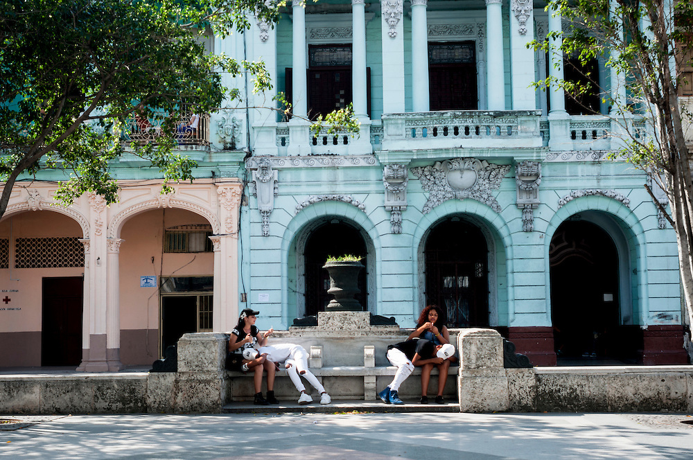 Teenagers in Havanna, Cuba rest and chat during a hot afternoon on a public bench.