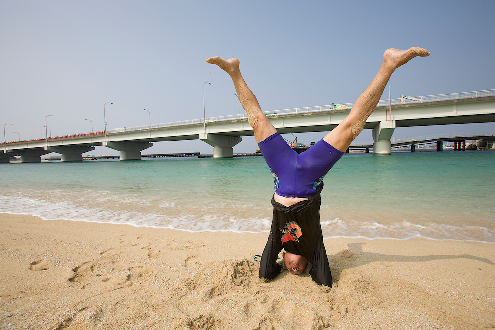 Fumiyasu Yamakawa, 84, begins his exercise regimen every day at 6 a.m. on a beach in Naha, Okinawa. He stretches, runs, swims, and does yoga, which includes standing on his head. After each workout, Fumiyasu lies on the sand to silently thank each part of his body for working properly. He claims that ten minutes of meditation is equivalent to three hours of sleep...Fumiyasu Yamakawa spent the first half of his life as a bank director. Now, he spends his mornings working out on the beach. Though Fumiyasu believes exercise keeps him fit, he claims smiling keeps him healthy..Here, Okinawn people live longer, but they also live better. They have powerful lessons to teach us about the optimal level of activity...If I did that, they'd need a five-gallon bucket to pick me up...Today we had a chance to meet Fumiyasu, the man who graced the cover of this month's National Geographic. He took me through his exercise regimen. You know what is most amazing, he was far more limber than I am. I can beat him in a foot race, though. But then again, I am 50 years younger than he is...This was beginning to look a lot like the regimen of an extreme American athlete, until we started the meditation. We thought about every single body part, and then we stood on our heads...Even though Fumiyasu represents a paradigm of physical fitness, the lessons Okinawans can teach us about aging, well probably looks more like what's going on behind us. It turns out as we age, strength, balance, and flexibility are more important than winning races. If you're over 50 years old and you break your hip, you have a 25 percent chance of dying within a year ..Here in Okinawa, they have about half the rate of broken hips that we do in America. Why is that? Okinawans teach us that it's the simple things that get us to a healthy old age. Things like gardening, getting up and down off the floor, or walking 30 or 40 minutes a day. Americans tend to do physical activities in big bursts. We go to the health club, w