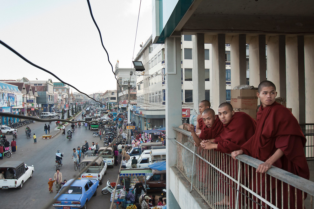 Four novice monks lean on the balcony rail in the central market of Taunggyi in Myanmar.
