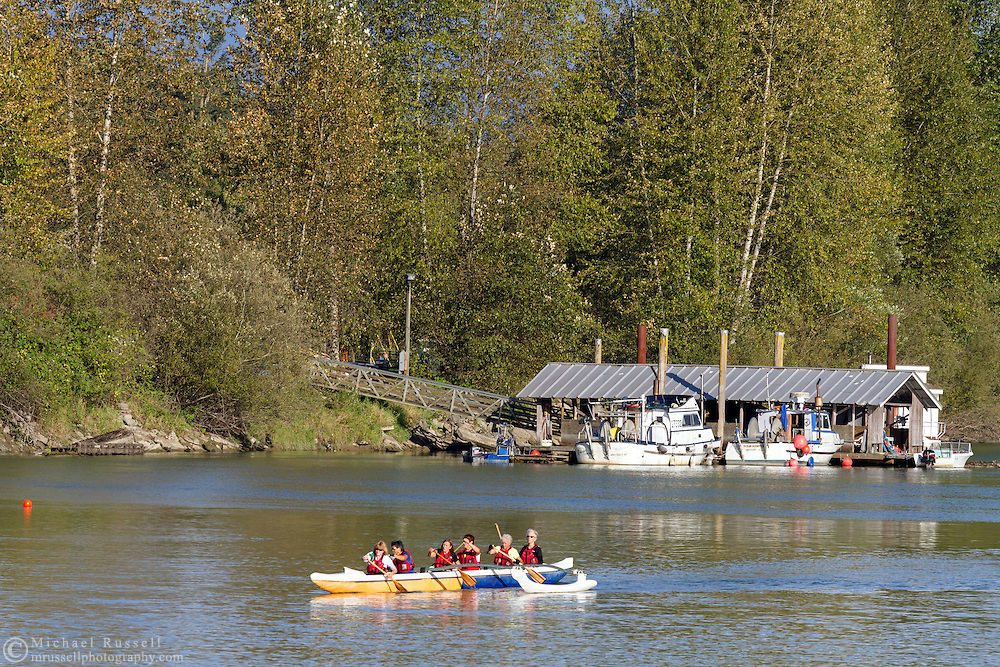Boaters from the Fort Langley Rowing Club paddle past docked fishing boats at the Bedford Channel in Fort Langley, British Columbia, Canada