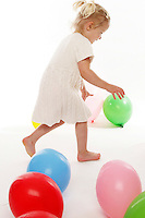 Two year old toddler girl chasing colorful balloons in the studio.