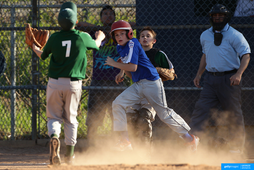 A young batter heads for face base as he skies a hit during the Norwalk Little League baseball competition at Broad River Fields,  Norwalk, Connecticut. USA. Photo Tim Clayton
