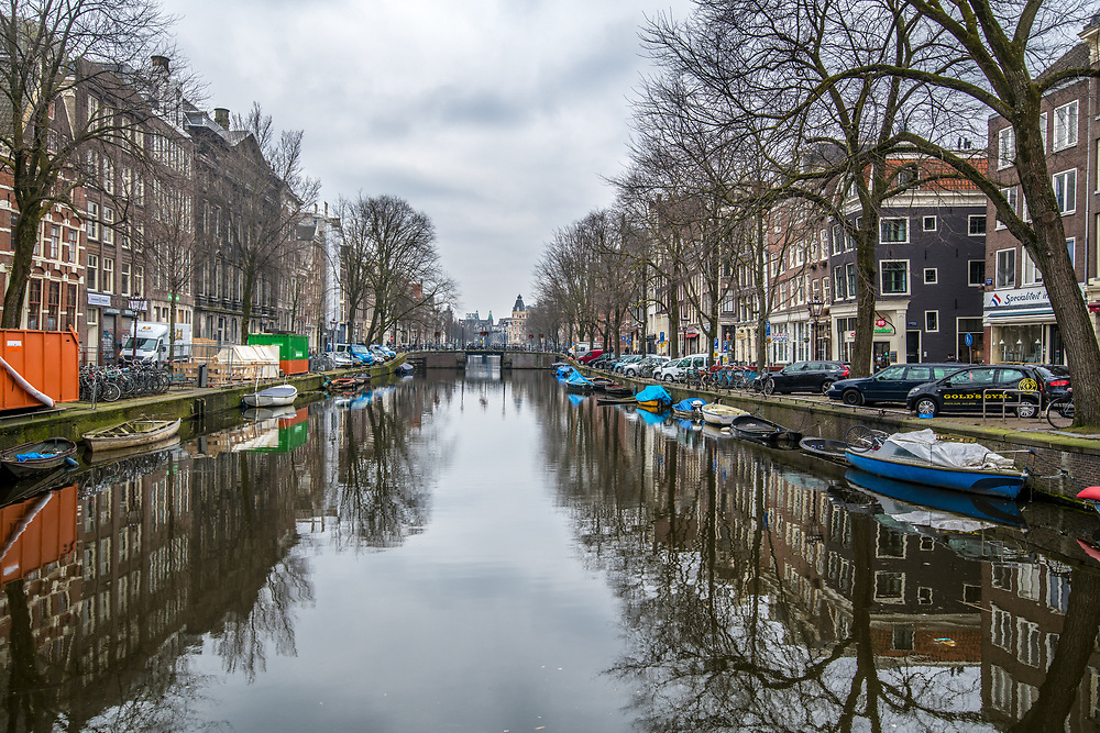 A canal cuts through neighborhood in Amsterdam with boats docked along its sides, Netherlands.