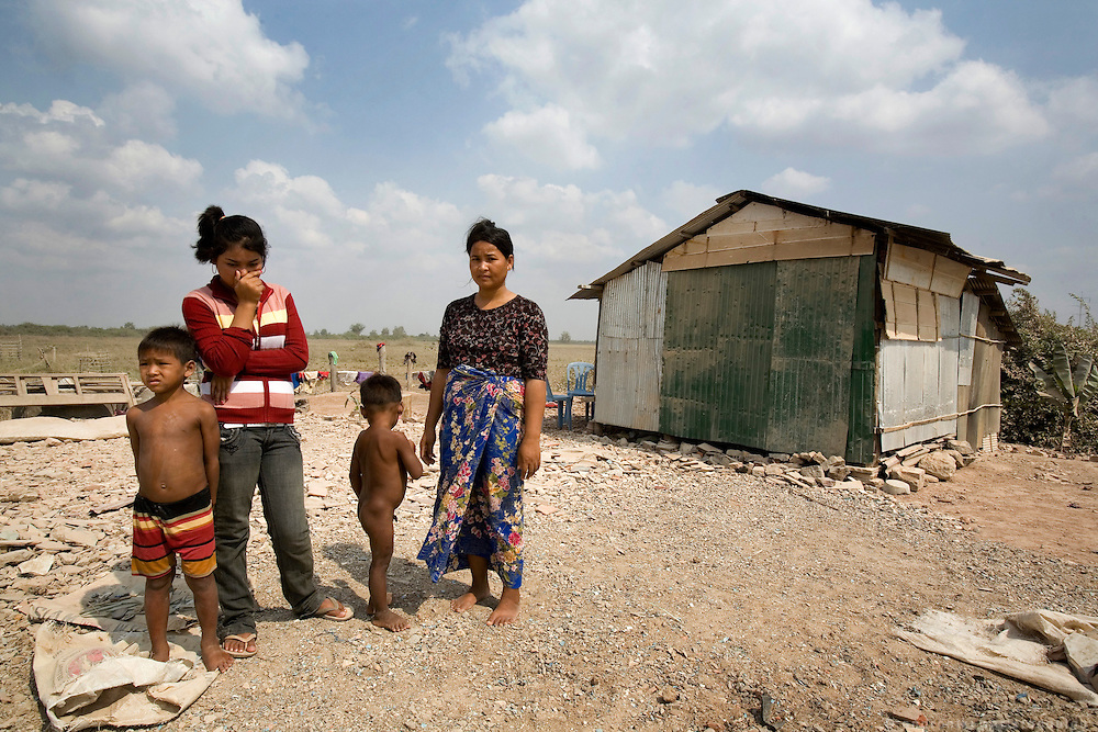 Rady with her step-mother Jan Cum Saang, her brother Yort (7) (L) and her younger brother Heir (4) (R) outside their home in a remote location outside Sisophon city.