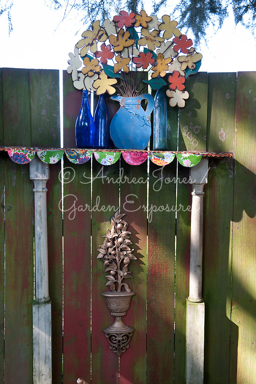 Wooden fence, columns, shelf with glass bottles and metal cut out flower bouquet<br /> <br /> Nancy Goldman's recycled garden (Nancyland), Portland, OR, USA