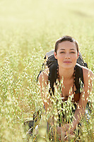 Female hiker squatting in long grass portrait