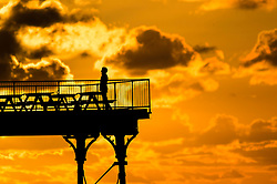 © London News Pictures. 24/02/2016. Aberystwyth, UK. <br /> A man  standing on the deck of the pier at sunset in Cardigan Bay in Aberystwyth on the west wales coast.. Photo credit: Keith Morris/LNP